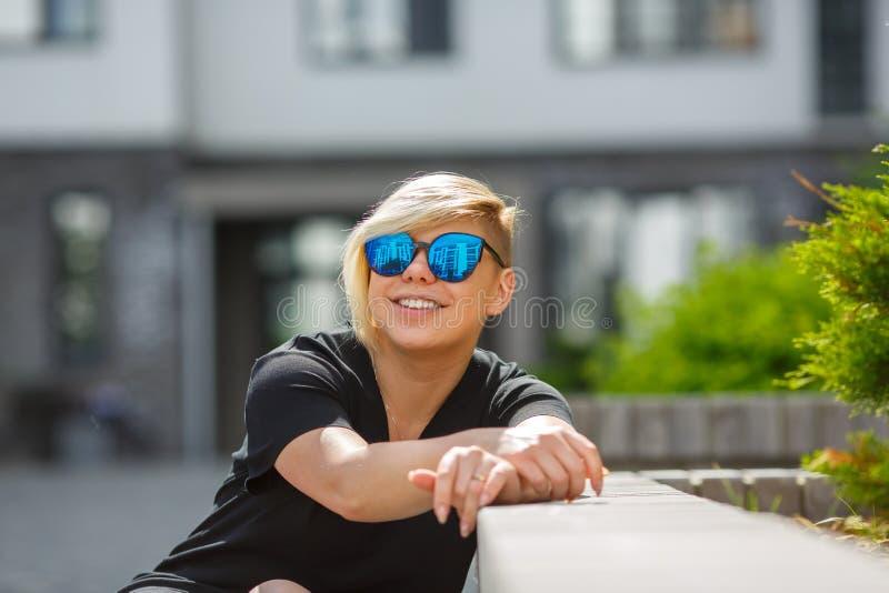 Meisje die in zonnebril helder glimlachen stock foto