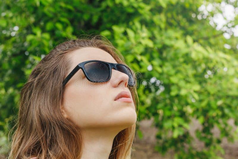 Meisje die in zonnebrilregen de hemel bekijken stock afbeelding