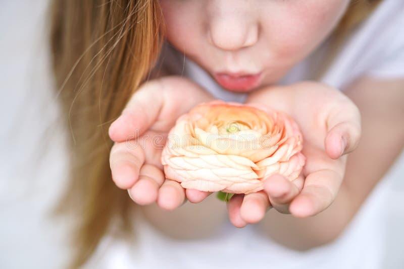 Meisje die zorgvuldig een mooie gevoelige bloem houden Kinderjarenbescherming stock foto's
