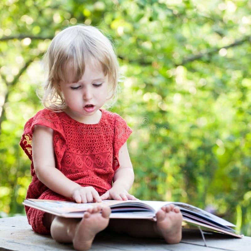 Meisje die zorgvuldig op een bank met de grote mening van de boekclose-up zitten royalty-vrije stock foto's