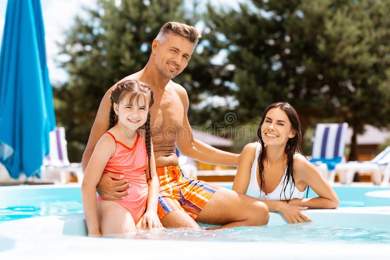 Meisje die zwemmend kostuum dragen die met ouders zwemmen stock foto