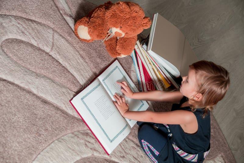 meisje in donkerblauwe het boekzitting van de kledingslezing op de vloer dichtbij teddybeer Het kind leest verhaal voor stuk spee stock foto's