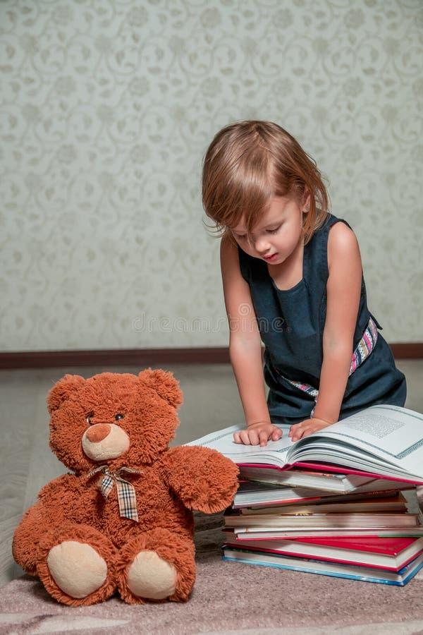 meisje in donkerblauwe het boekzitting van de kledingslezing op de vloer dichtbij teddybeer Het kind leest verhaal voor stuk spee royalty-vrije stock afbeelding