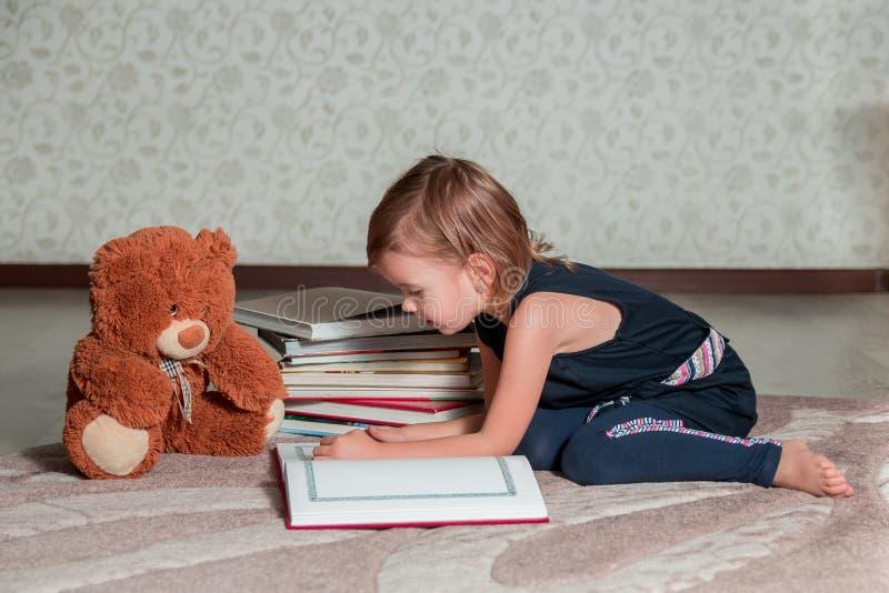 meisje in donkerblauwe het boekzitting van de kledingslezing op de vloer dichtbij teddybeer Het kind leest verhaal voor stuk spee royalty-vrije stock afbeeldingen