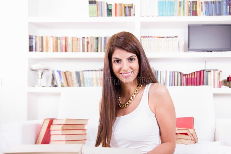 Meisje door boeken dat te glimlachen wordt omringd stock fotografie