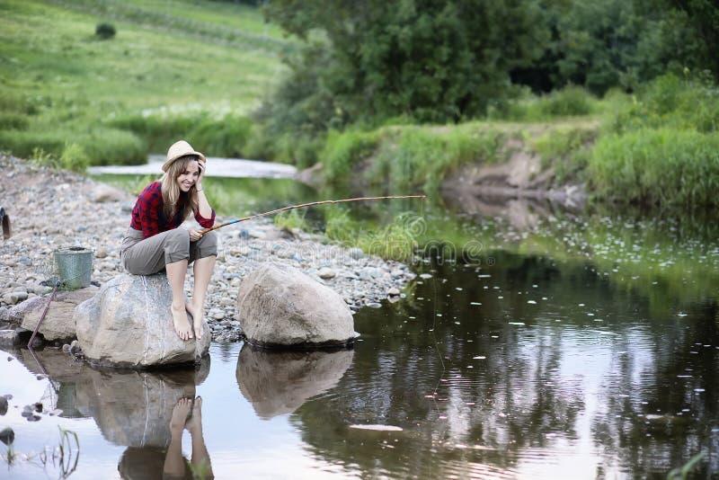 Meisje door de rivier met een hengel royalty-vrije stock foto's