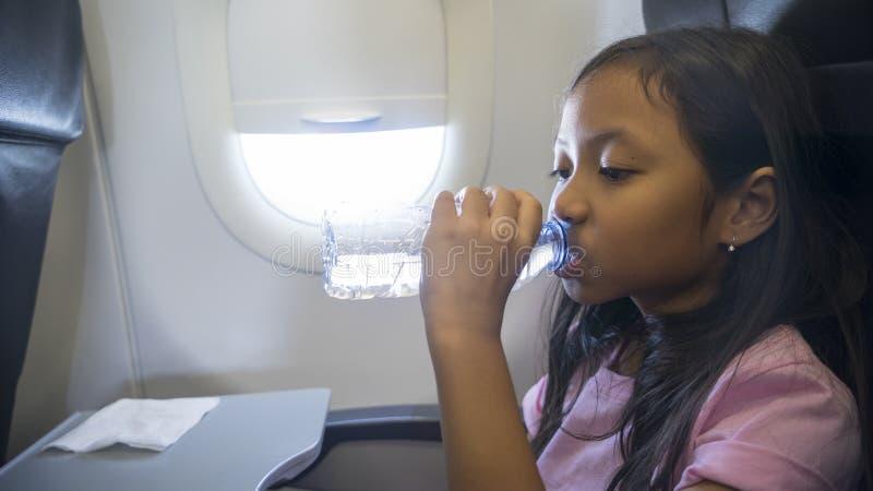 Meisje drinkwater in vliegtuig stock afbeeldingen