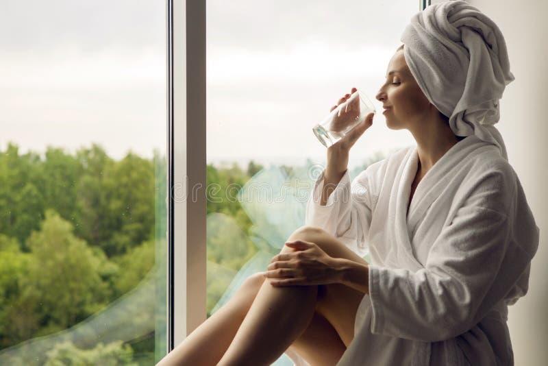 Meisje in een badjas en handdoek op hoofdzitting royalty-vrije stock fotografie