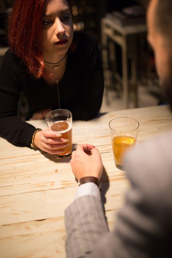 Meisje in een bar die aan zijn vriend het drinken ambachtbier luisteren stock afbeeldingen