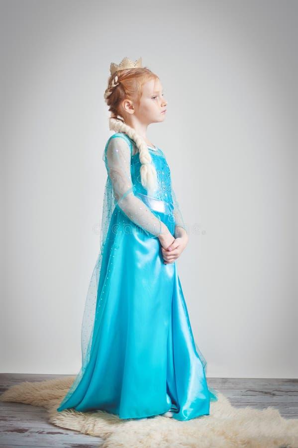 Meisje in een blauwe kleding met een gouden kroon royalty-vrije stock foto