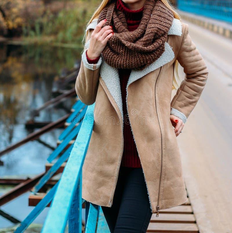 Meisje in een bruin jasje dichtbij de rivier en een bruine sjaal, snod de herfst, gebreide met de hand gemaakte dingen, royalty-vrije stock foto's