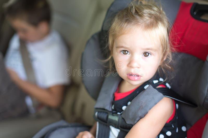 Meisje in een Childs-Veiligheidszetel die wordt vastgebonden stock fotografie