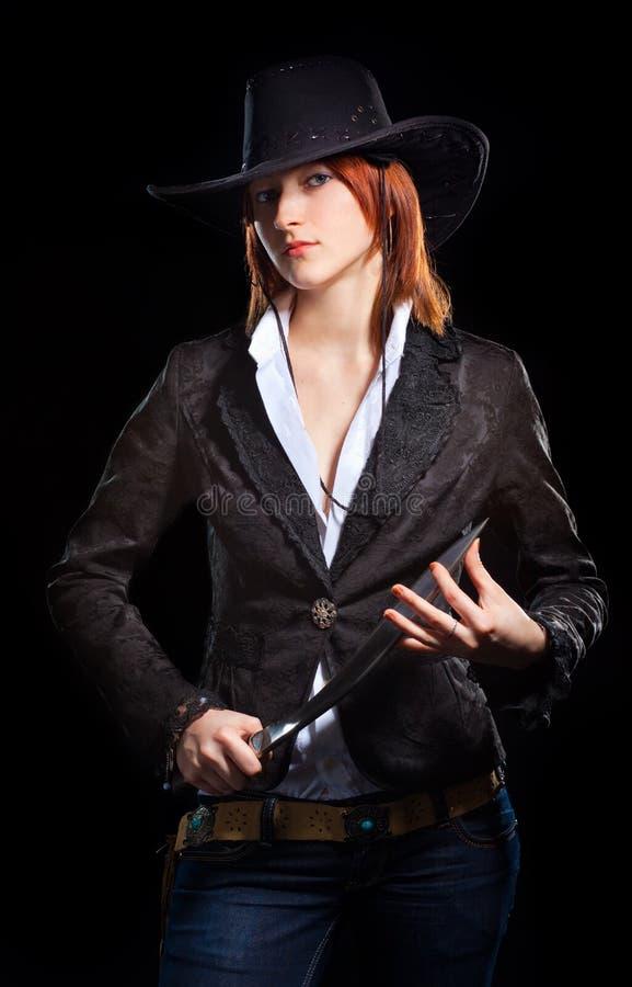 Meisje in een cowboyhoed met een mes stock afbeelding
