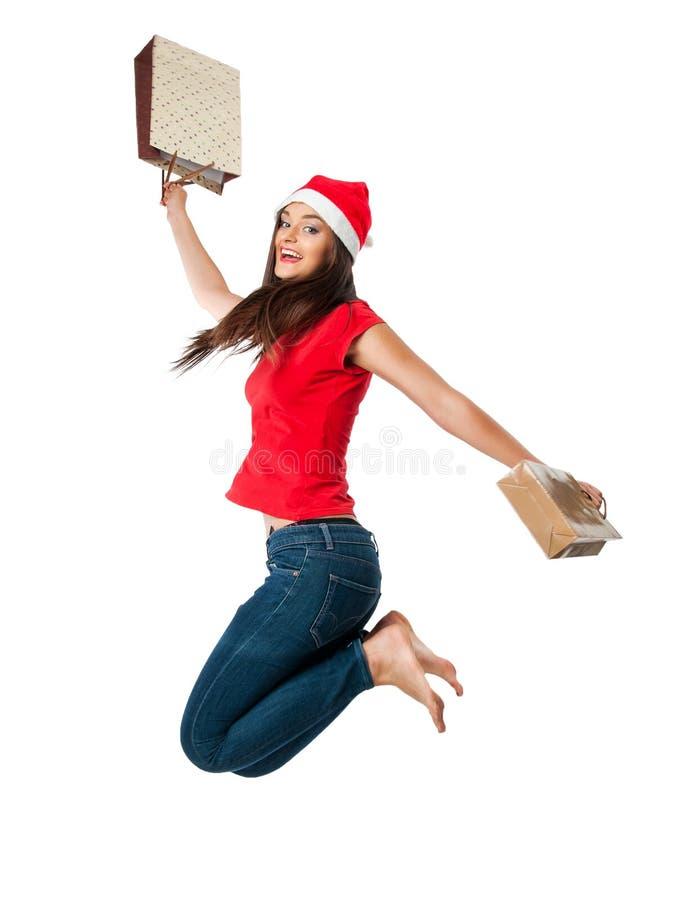 Meisje in een de helperhoed die van de Kerstman en het winkelen zakken springen houden royalty-vrije stock fotografie
