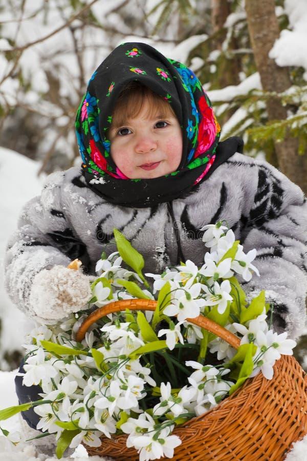 Meisje in een de winterhout met de grote mand van sneeuwklokjes stock afbeeldingen