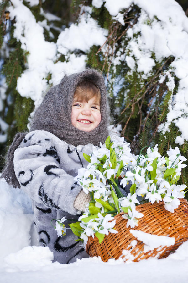 Meisje in een de winterhout met de grote mand van sneeuwklokjes stock foto's