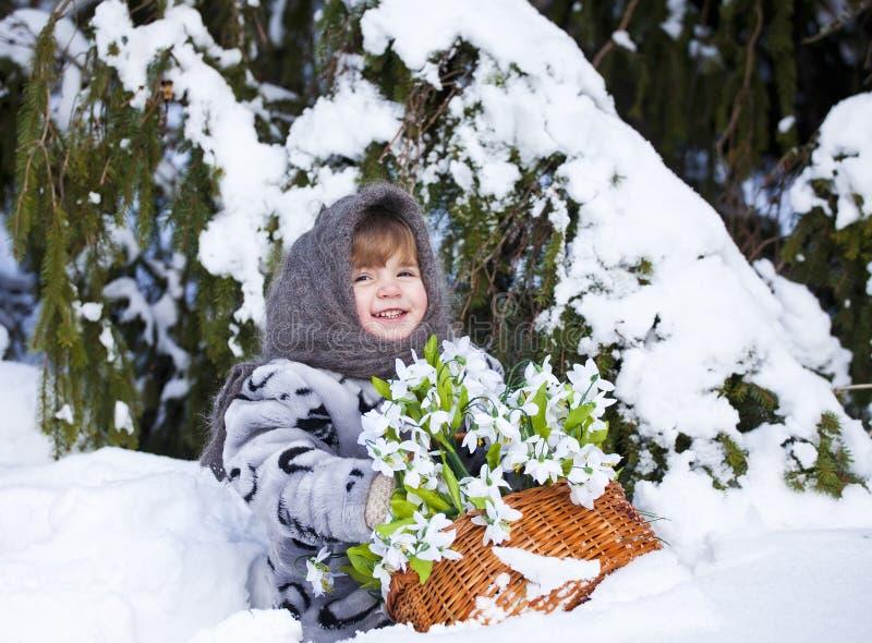 Meisje in een de winterhout met de grote mand van sneeuwklokjes stock fotografie