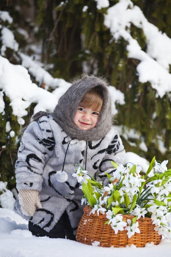 Meisje in een de winterhout met de grote mand van sneeuwklokjes stock afbeelding