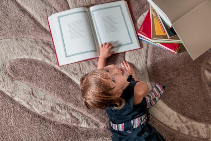 Meisje in een donkerblauw boek die van de kledingslezing op de vloer liggen Hoogste mening Het bekijken de camera stock afbeelding