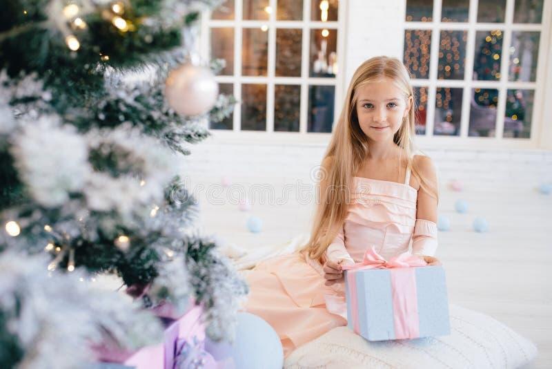 Meisje in een elegante roze de giftdoos van de kledingsholding dichtbij Kerstboom stock afbeelding