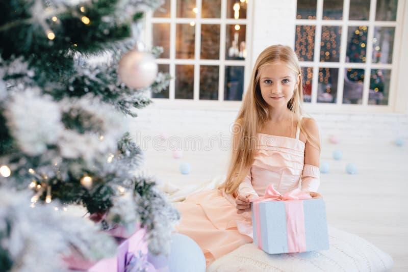 Meisje in een elegante roze de giftdoos van de kledingsholding dichtbij Kerstboom stock foto's