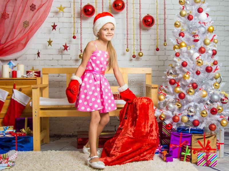 Meisje in een GLB en vuisthandschoenen van Santa Claus met een zak van Kerstmisgiften stock afbeelding