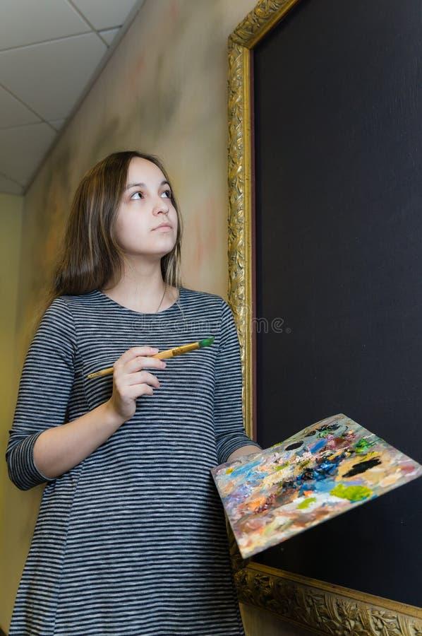 Meisje in een grijze kleding met een leeswijzer en palet voor het canvas royalty-vrije stock afbeeldingen