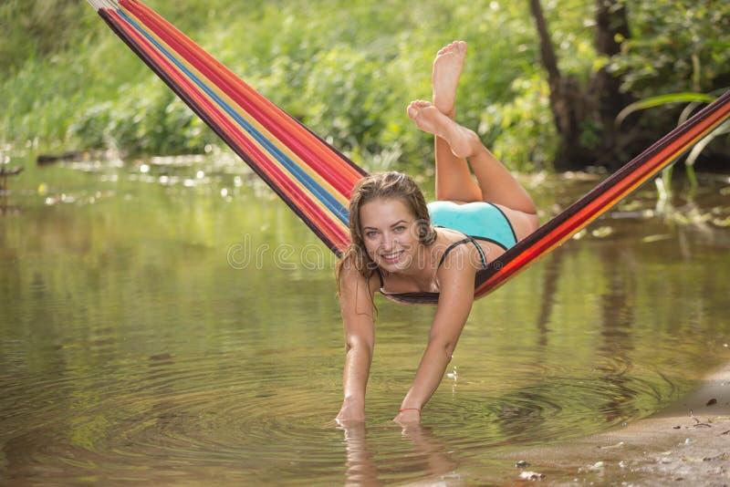 Meisje in een hangmat over het water royalty-vrije stock afbeeldingen