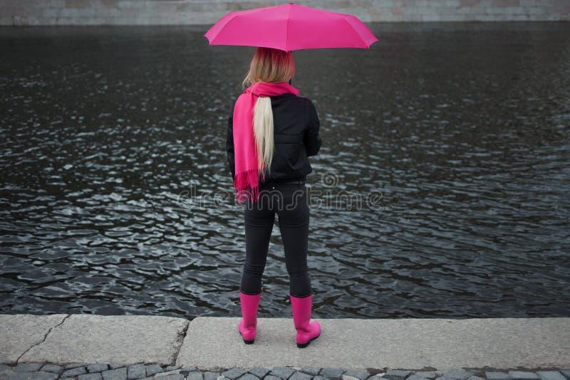 Meisje in een heldere roze sjaal, rubberlaarzen en paraplu die zich op de banken van de rivier, rug bevinden Grijs onverbiddelijk stock fotografie