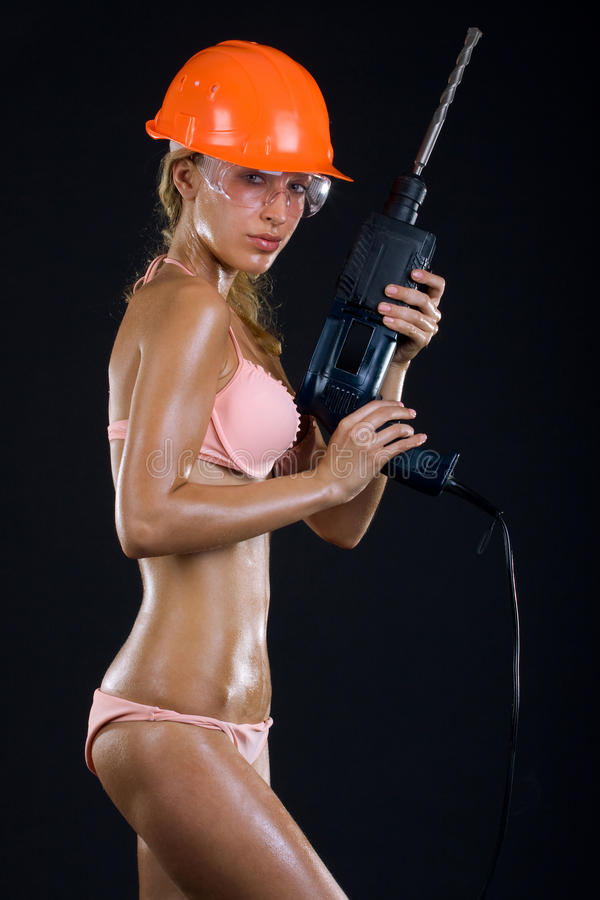 Meisje in een helm met een boor stock afbeeldingen