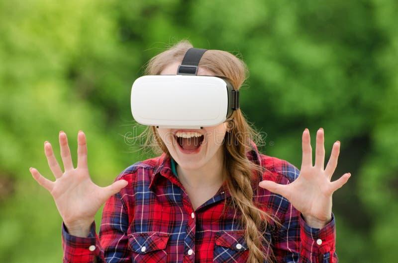 Meisje in een helm van virtuele werkelijkheid op een achtergrond van aard D stock fotografie