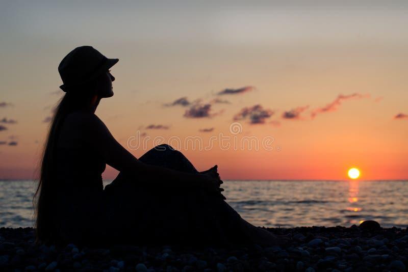 Meisje in een hoedenzitting op een achtergrond van het overzees bij zonsondergang Silhouet royalty-vrije stock afbeelding