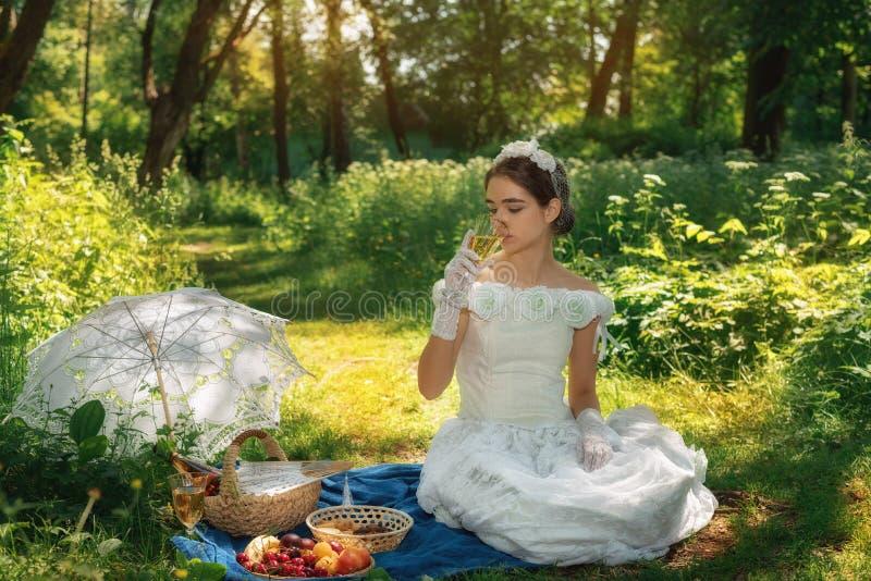 Meisje in een huwelijkskleding in het park op een zonnige dag op een picknick met royalty-vrije stock foto