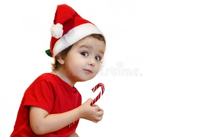 meisje in een kersthoed en rode jurk baby eet een snoepriet met eetlust , kijkt uit en ziet er eng uit kerstsnoepjes en cadeau royalty-vrije stock afbeeldingen