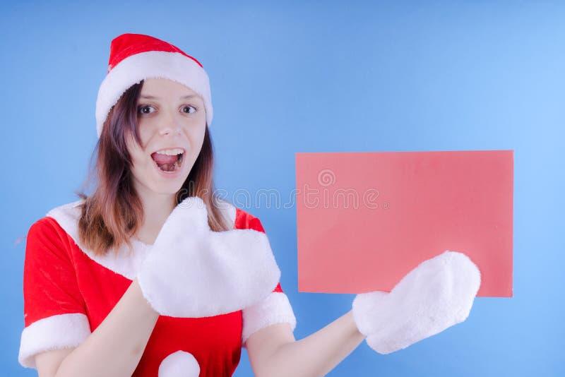 Meisje in een kostuum ` Santa Claus ` met een teken op een blauwe achtergrond Het concept kortingen en verkoop voor Kerstmis Kort stock afbeelding