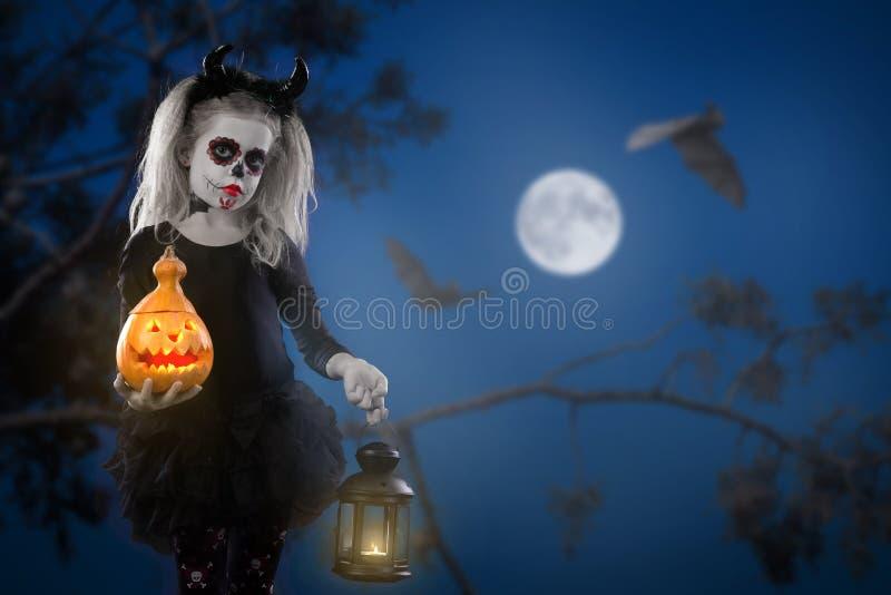 Meisje in een kostuum van heks het stellen met pompoenen over feeachtergrond Halloween stock fotografie