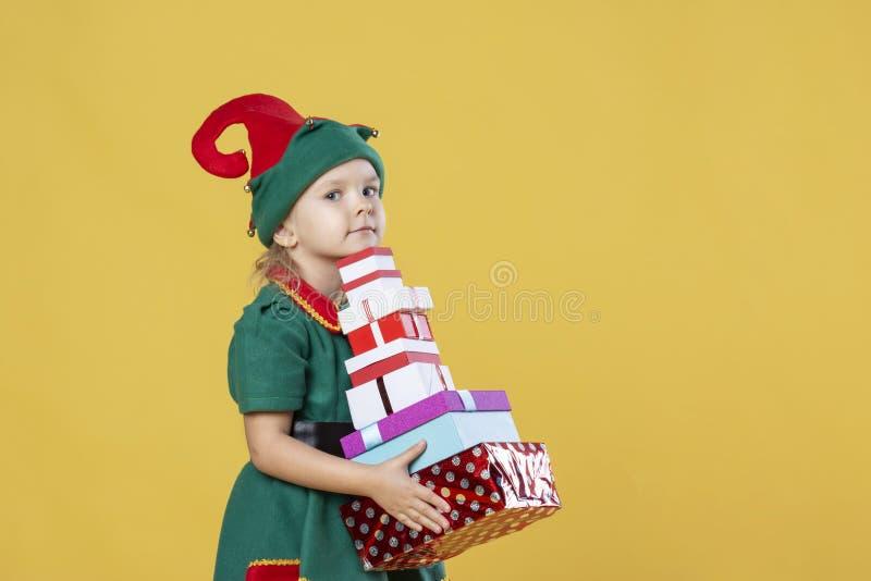 Meisje in een kostuum van het Kerstmiself op een gele achtergrond Een kind houdt een stapel van voorstelt stock foto's