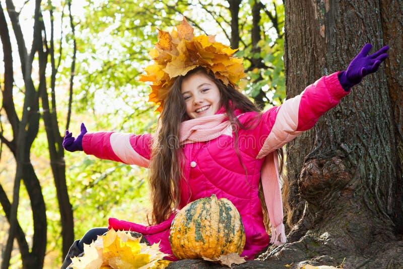 Meisje in een kroon van esdoornbladeren in park stock afbeeldingen
