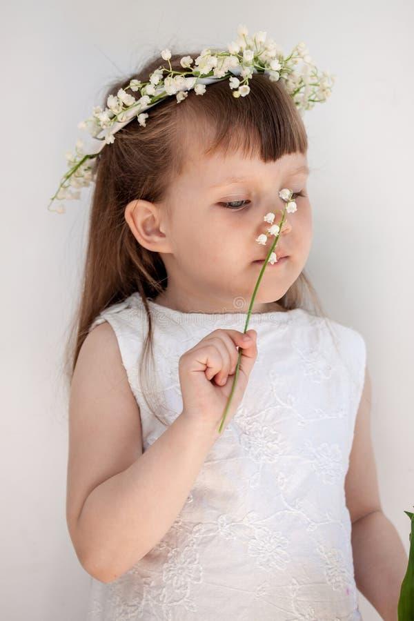 Meisje in een kroon van lelietje-van-dalen stock foto