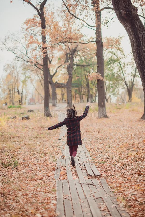Meisje in een laag die de weg in het de herfstpark weglopen royalty-vrije stock foto