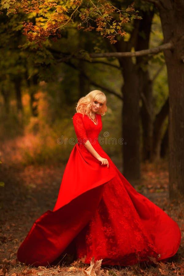 Meisje in een lange rode kleding in het de herfstbos stock afbeelding