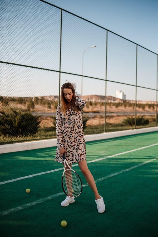 Meisje in een mooie kleding met een racket in haar handen op de tennisbaan stock foto's
