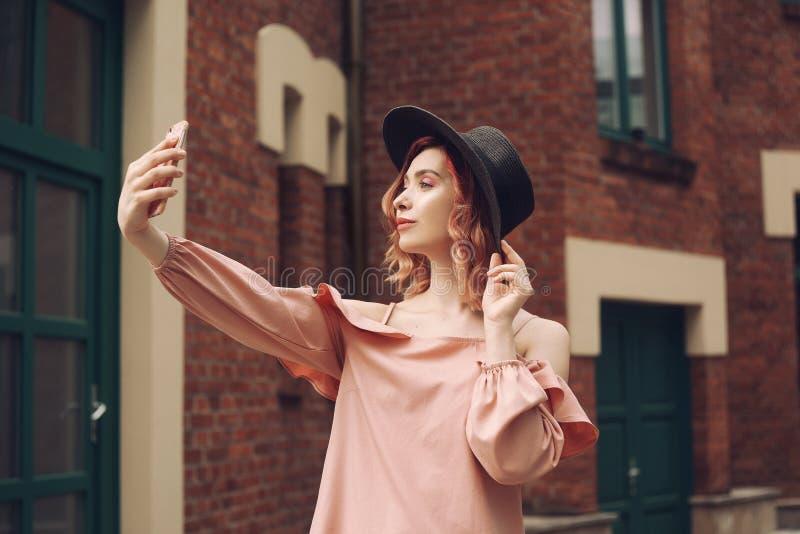 Meisje in een mooie roze kleding en een zwarte hoed Het meisje met roze krullend haar reist Een meisje maakt een foto op een smar royalty-vrije stock afbeelding