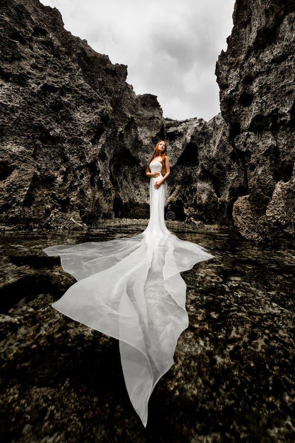 Meisje in een overzeese die kreek door klippen wordt omringd stock afbeeldingen