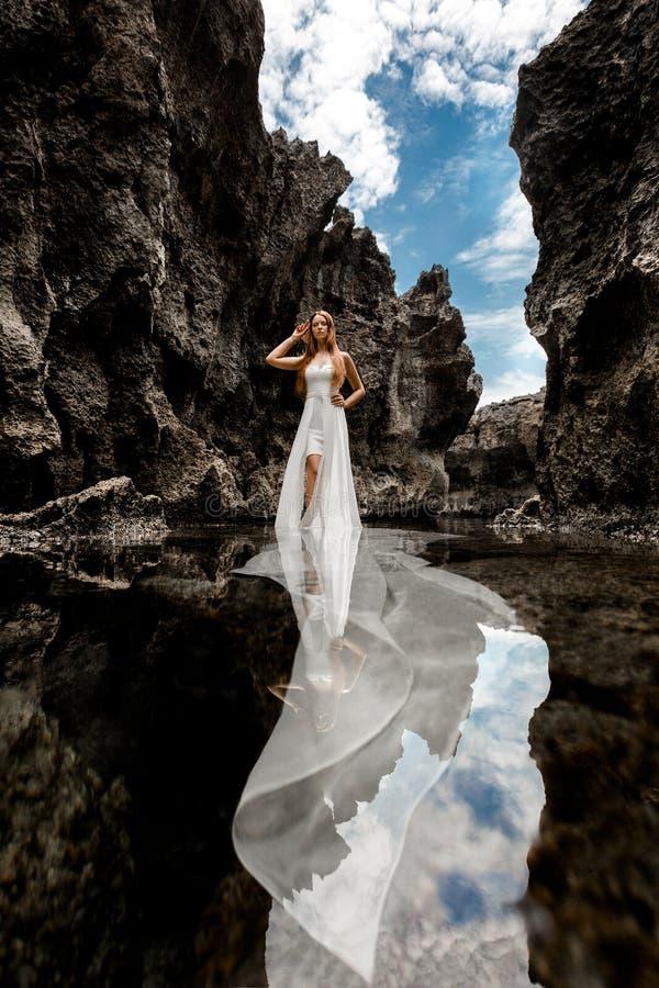 Meisje in een overzeese die kreek door klippen wordt omringd royalty-vrije stock fotografie