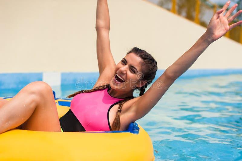Meisje in een poolzitting in een rubber opblaasbare vlotter stock foto