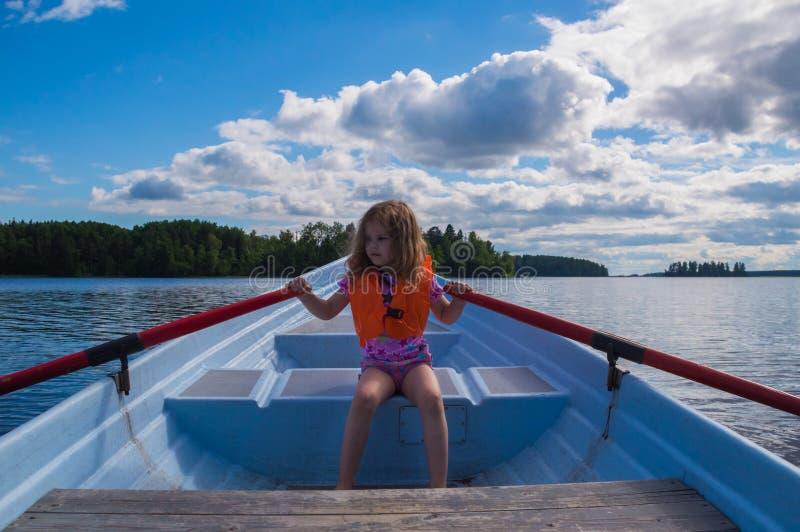 Meisje in een reddingsvest, een kind in een boot, het roeien roeispanen stock foto's