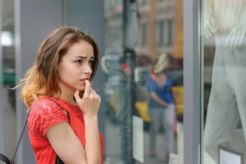 Meisje in een rode blouse die zich pensively bevinden dichtbij storefront royalty-vrije stock foto