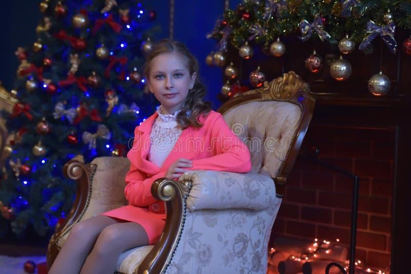 Meisje in een roze kostuum in Kerstmis stock afbeelding