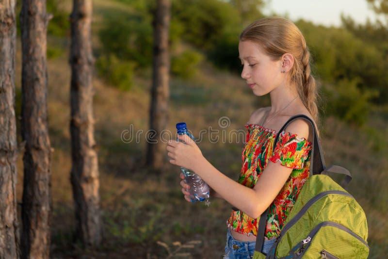 Meisje in een stijging met een rugzak, die een fles water, rust in het hout houden, concept stock foto